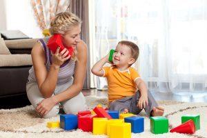 Довольный малыш играет с мамой в кубики